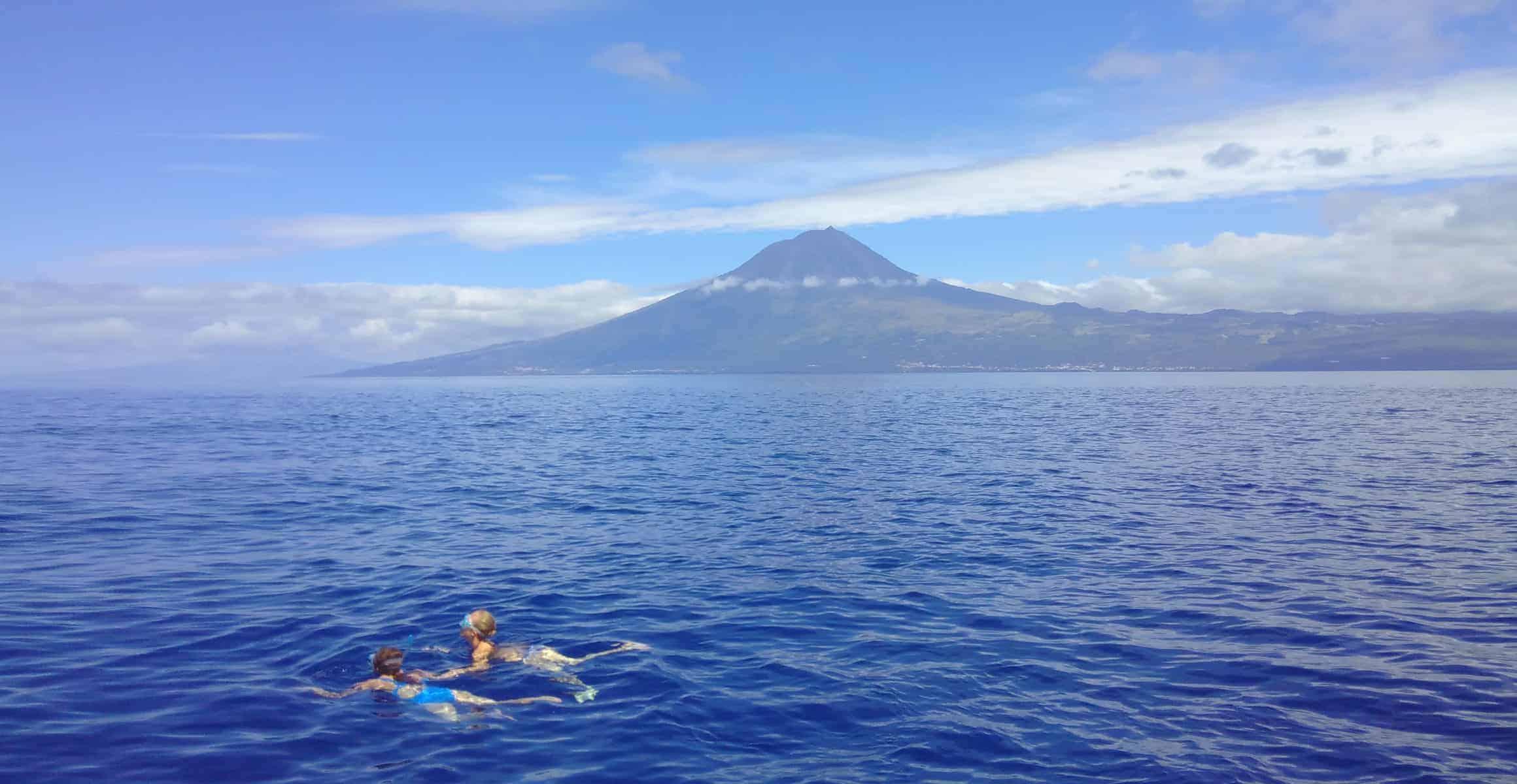 Zwei Menschen schwimmen bei Heilreise mit Taucherbrille im Meer vor der Azoren Insel Pico im Hintergrund der Vulkan