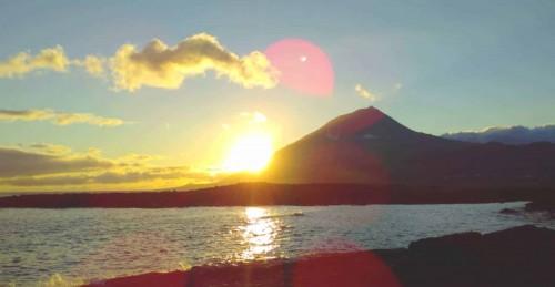 Malerischer Sonnenuntergang auf der Azoren Insel Pico. Die Sonne geht links vom Vulkan langsam unter im Vordergrund ist das ruhige Meer