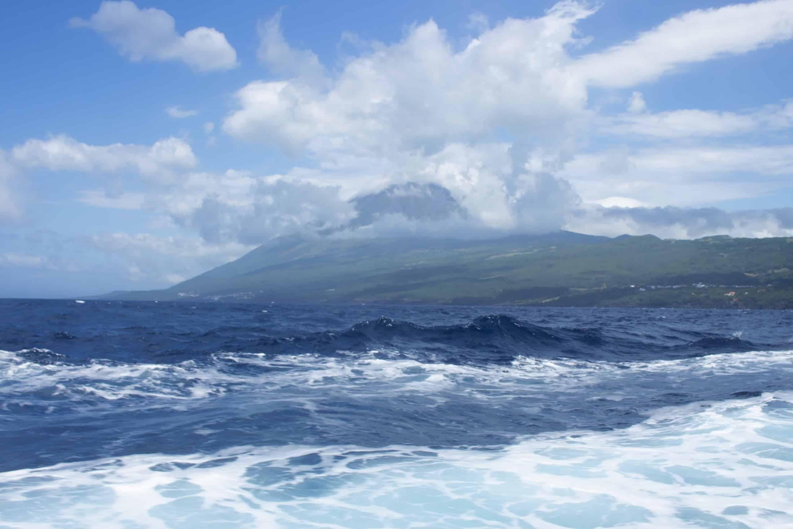 Insel Vulkan Ponta do Pico auf den Azoren in Wolken gehüllt und im Vordergrund das Meer mit starkem Wellengang