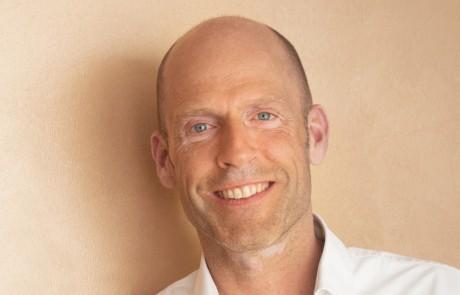 Geistiger Heiler Dirk Heilenmann sitzt im weißen Hemd im loulan in Lüneburg