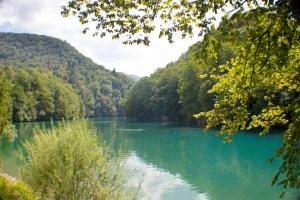 Wandern während des Natur-Retreat in Slowenien. Das Bild zeigt einen blauen See mit grünen Bäumen