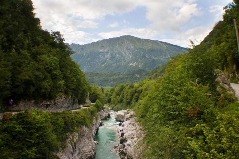 Wandern während der Heilreise in Slowenien zeigt im Vordergrund das Tal mit Wald und Wiese und im Hintergrund beeindruckende Berge